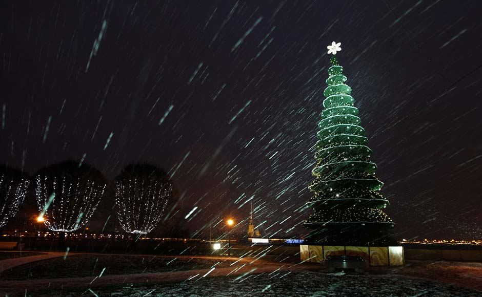 A lit Christmas tree is seen amidst snowfall in St Petersburg. Reuters