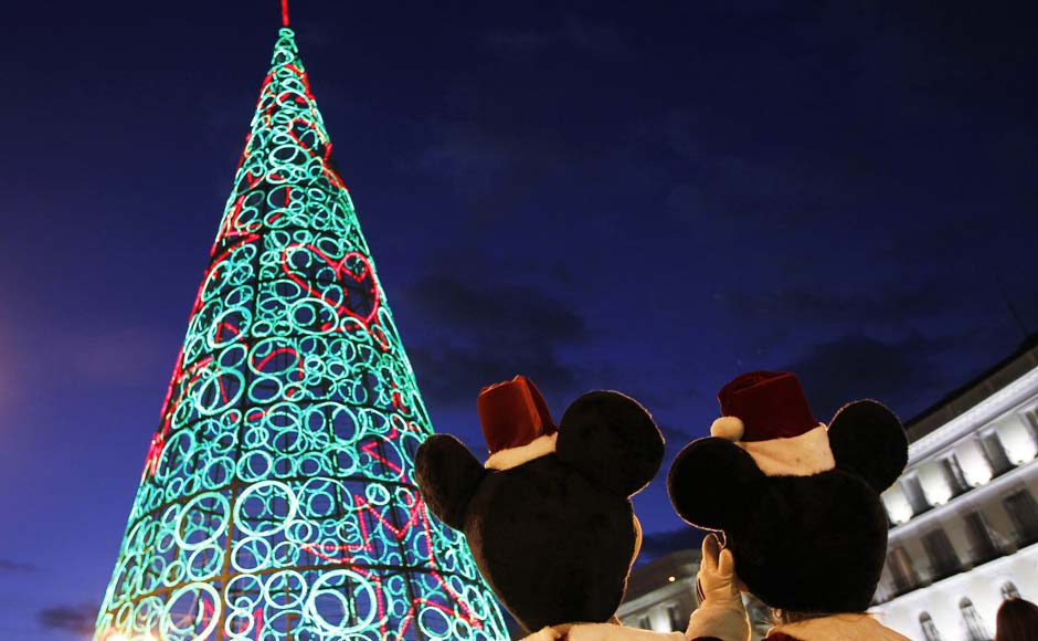 Two people dressed as Mickey Mouse stand next to a Christmas tree made out of lights in Spain. Reuters