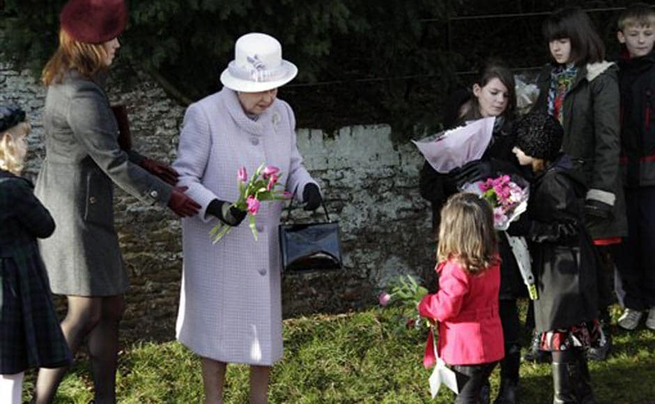 Britain's Queen Elizabeth II, receives flowers from children after she and other members of the royal family attended a Christmas Service at St Mary's church in the grounds of Sandringham Estate, the Queen's Norfolk retreat, England. AP
