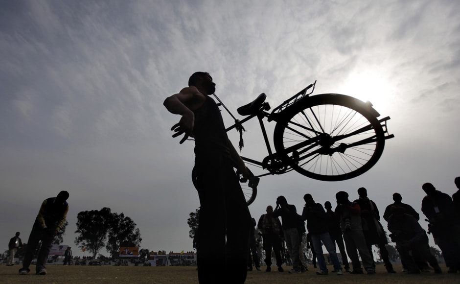 A villager lifts a bicycle with his teeth as he performs during  the rural sports festival, on Saturday. AP