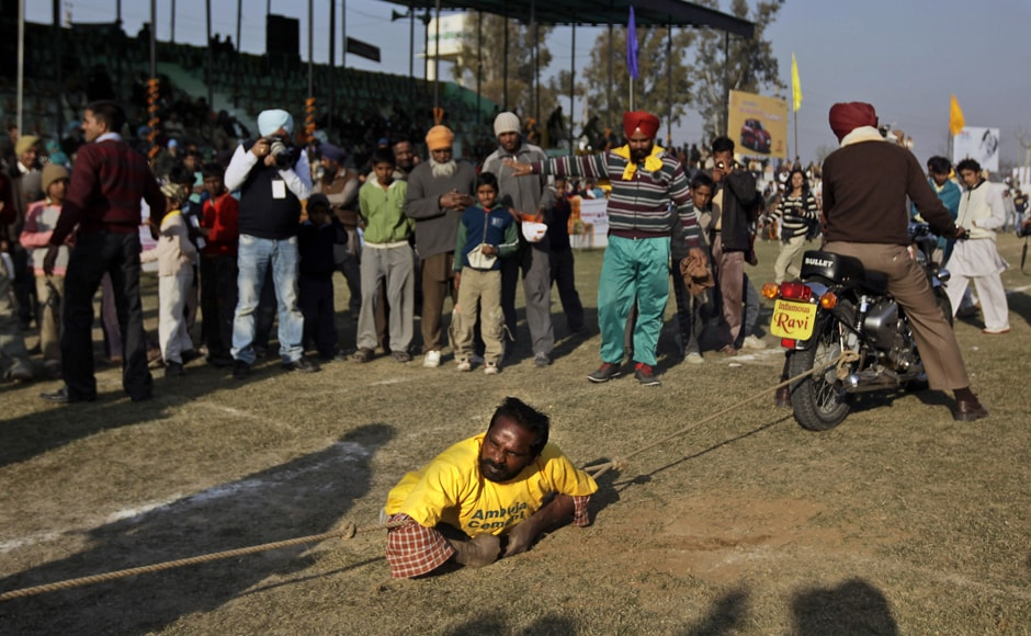 A physically challenged villager displays a feat of strength by stopping two motorbikes with ropes, during the Kila Raipur Sports Festival. AP