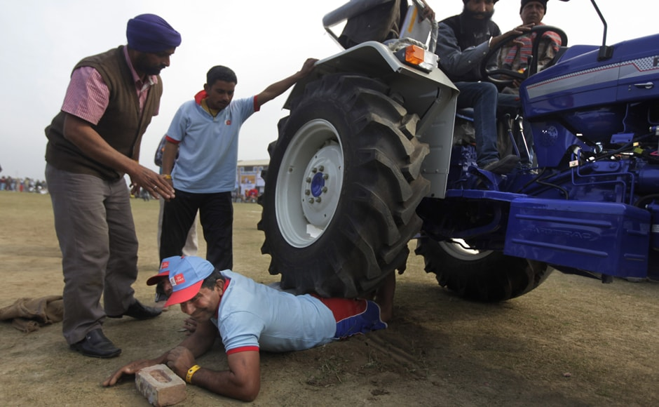 In a show of strength, two men lie on the grounds and allow a tractor carrying three adults to pass over them. AP