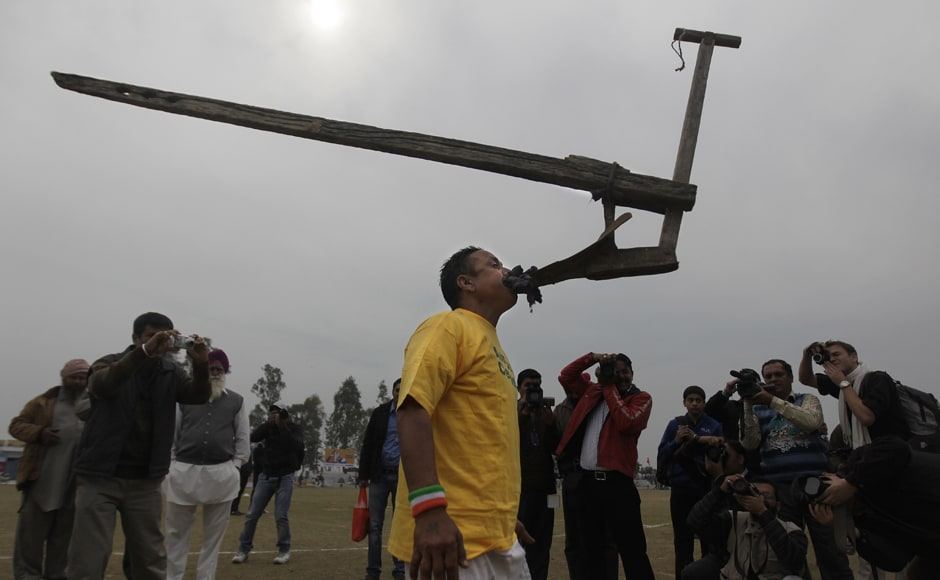 A villager balances a plough in his mouth during the rural sports festival. AP