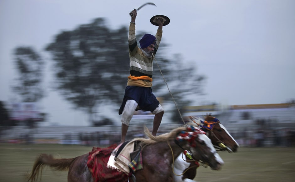 "A Sikh warrior rides on two horses during a rural sports festival, also known as ""Indian Rural Olympics"". AP"