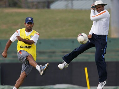 File picture of India's captain Dhoni kicking a soccer ball past Virender Sehwag. Reuters