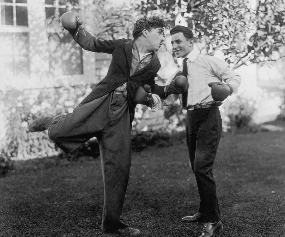 Charlie Chaplin (Sir Charles Spencer Chaplin, 1889 - 1977), English film actor and director larking with British flyweight boxer Harry Mansell. Getty Images