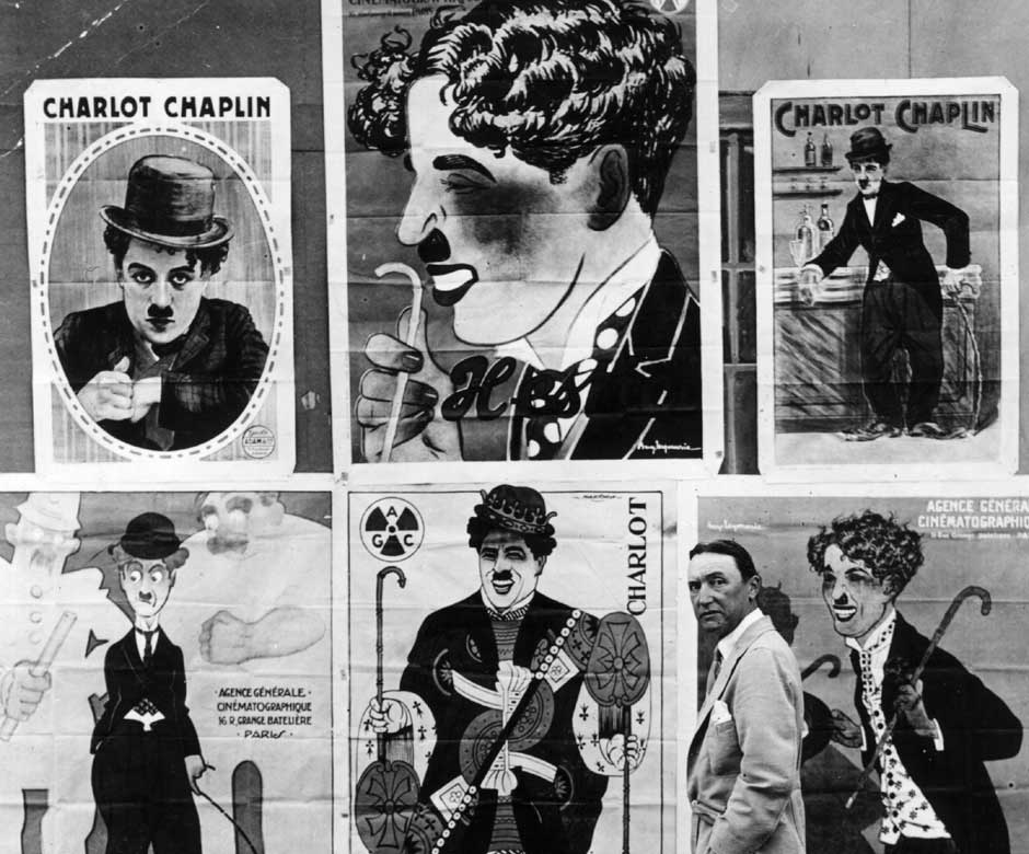 Alfred Reeves with a selection of French posters advertising Charlie Chaplin films. Getty Images