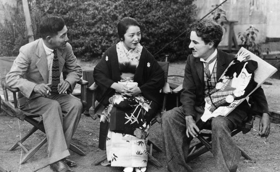 English actor Sir Charlie Chaplin, (right), receives a portrait of himself from a Japanese actress and her husband, painted by a Japanese artist. Getty Images