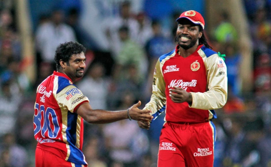 Royal Challengers Banglore's Muttiah Muralitharan, left and Chris Gayle celebrate the wicket of Mumbai Indians Dwayne Smith. AP