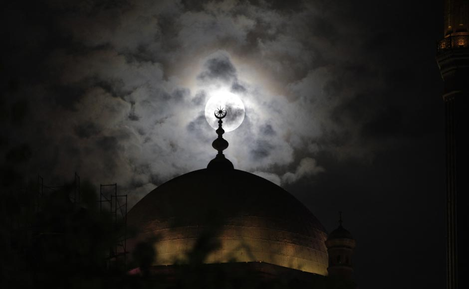 A full moon is seen behind the minaret of Mohamed Ali mosque, in Islamic Cairo. Reuters