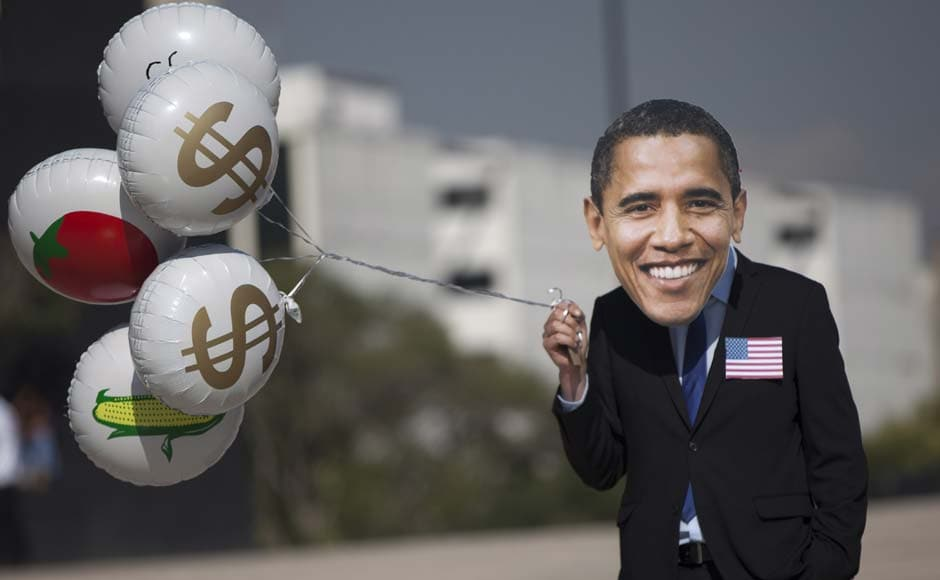 An Oxfam activist wears a mask depicting President Barack Obama holds balloons decorated with dollar signs and food during a protest in Mexico City. Alexandre Meneghini/AP