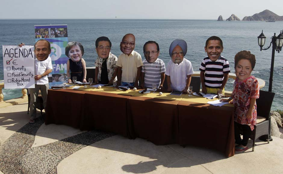 Oxfam activists wear masks representing some of the G20 world leaders along the shore in Los Cabos. Andres Stapff/Reuters