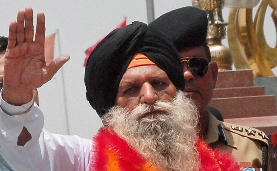 Surjit Singh waves on his arrival at the Indian side of Attari-Wagah border. PTI