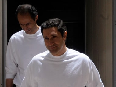 Mubarak's sons Gamal and Alaa Mubarak walk after being sentenced in Cairo. Reuters