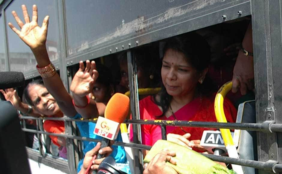 Kanimozhi in a bus waving to DMK supporters. Firstpost