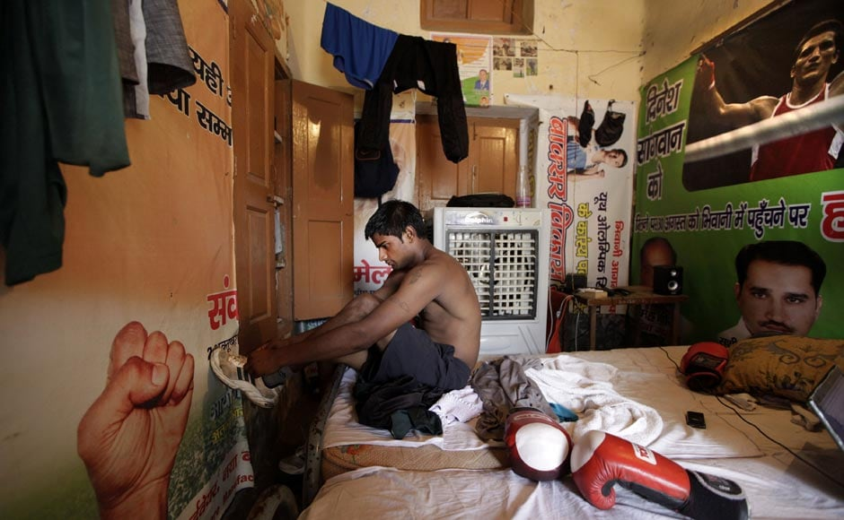 An amateur boxer gets ready for a training session in his room at the Sports Authority of India complex, in Bhiwani. AP