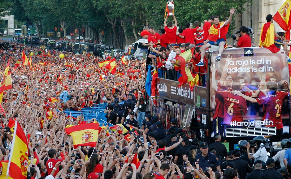Spain's players hold up the trophy to the crowd. Captain Iker Casillas is seen right in front of the bus. Reuters