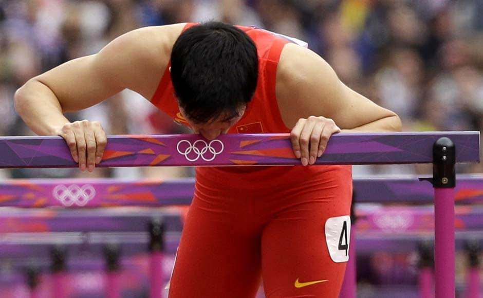 China's Liu Xiang kisses his hurdle after falling in a men's 110-meter hurdles heat during the athletics. The Chinese star athlete won the gold in the same event in 2004. His hopes were dashed by injury in 2008. AP