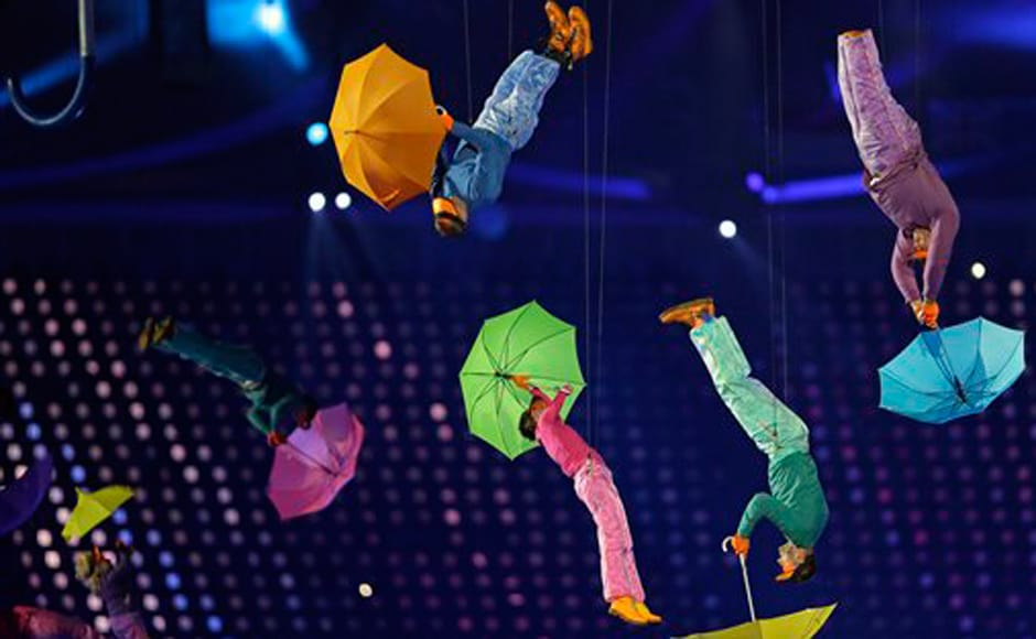 Performers with umbrellasare suspended in the air. AP