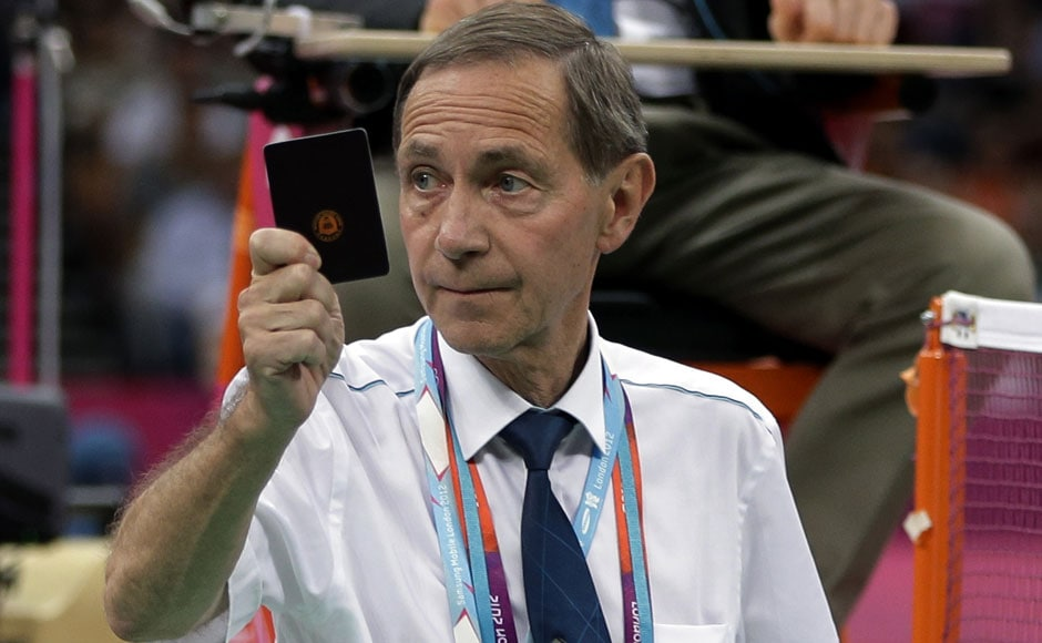 Head badminton referee Torsten Berg issues a black card to players in the women's doubles badminton match between Ha Jung-eun and Kim Min-jung, of South Korea, and Meiliana Jauhari and Greysia Polii, of Indonesia.AP
