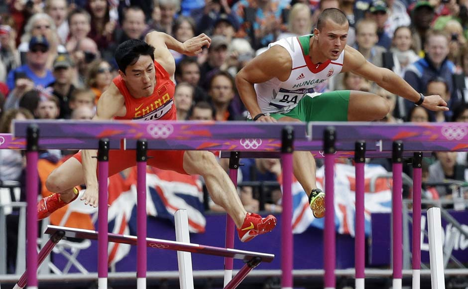 China's Liu Xiang, left, fails to clear a hurdle in a men's 110-meter hurdles heat as he competes alongside Hungary's Balazs Baji during the athletics in the Olympic Stadium. AP