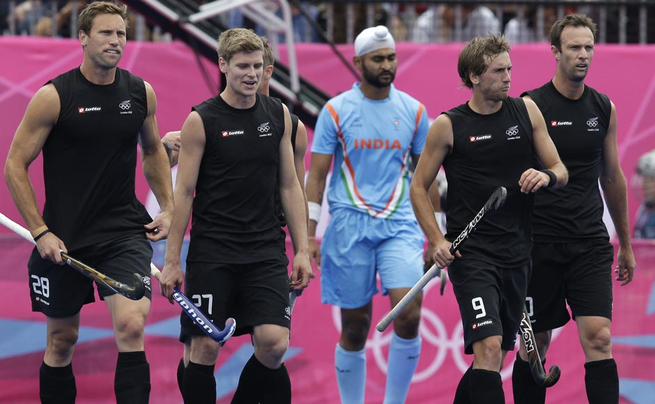 New Zealand's Richard Petherick (28), Stephen Jenness (27), Blair Hilton (9) and Ryan Archibald walk to resume the play following a goal by Phillip Burrows, unseen, during their men's hockey preliminary match against India. New Zealand won 3-1. In centre, in blue is India's Sandeep Singh.Bullit Marquez/AP