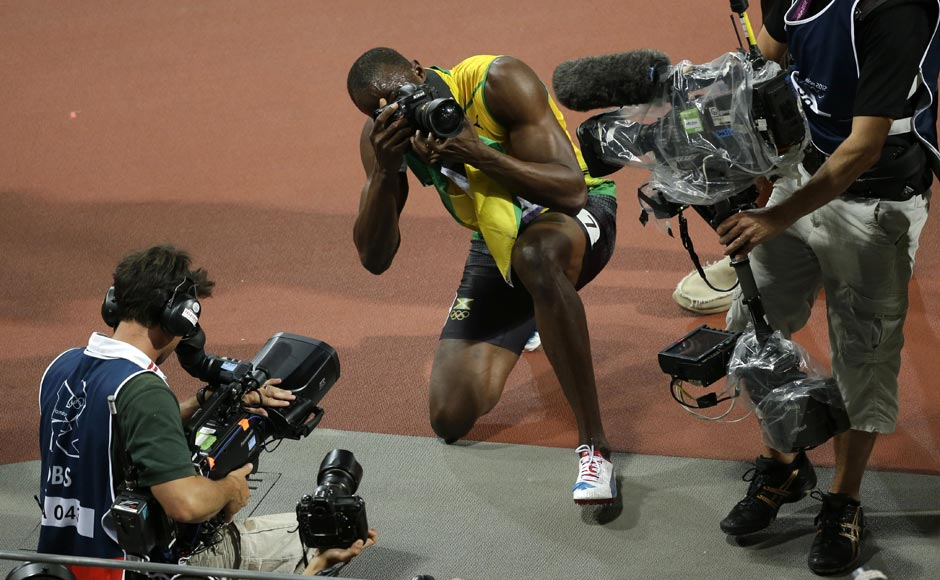 Jamaica's Usain Bolt, center, takes photographs after he won gold in the men's 200-meter final during the athletics.Charlie Riedel/AP