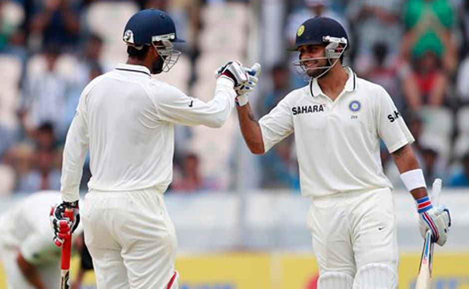 Virat Kohli, right, congratulates teammate Cheteshwar Pujara for scoring a half century during the first day of the first crickettest match against New Zealand in Hyderabad. AP