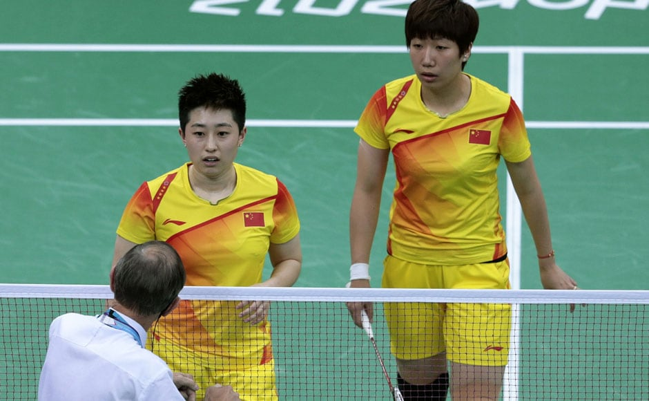 An unidentified official talks to world doubles champions Yu Yang, left, and Wang Xiaoli, as South Korea's Jung Kyung-eun, right, and Kim Ha-na, listen during their women's doubles badminton match at the 2012 Summer Olympics.AP