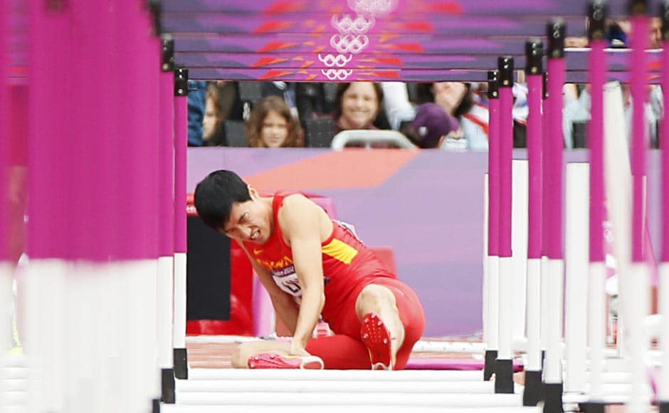 China's Liu Xiang sits on the track after suffering an injury in his men's 110m hurdles round 1 heat. Reuters