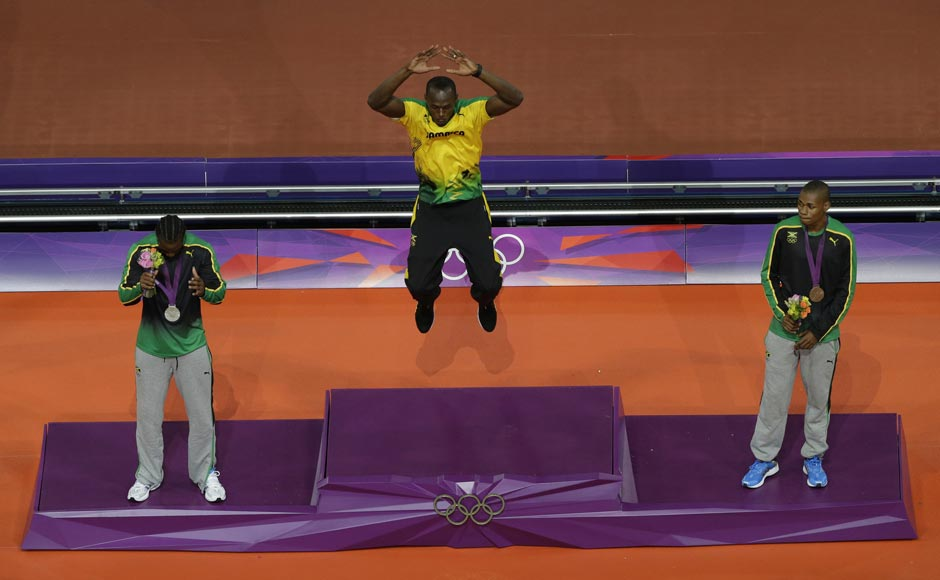 Jamaica's Usain Bolt (C) jumps on the podium with his gold medal as compatriots Yohan Blake shows his silver medal and Warren Weir (R) shows his bronze during the presentation ceremony for the men's 200m event at the London 2012 Olympic Games at the Olympic Stadium.Cathal McNaughton/Reuters