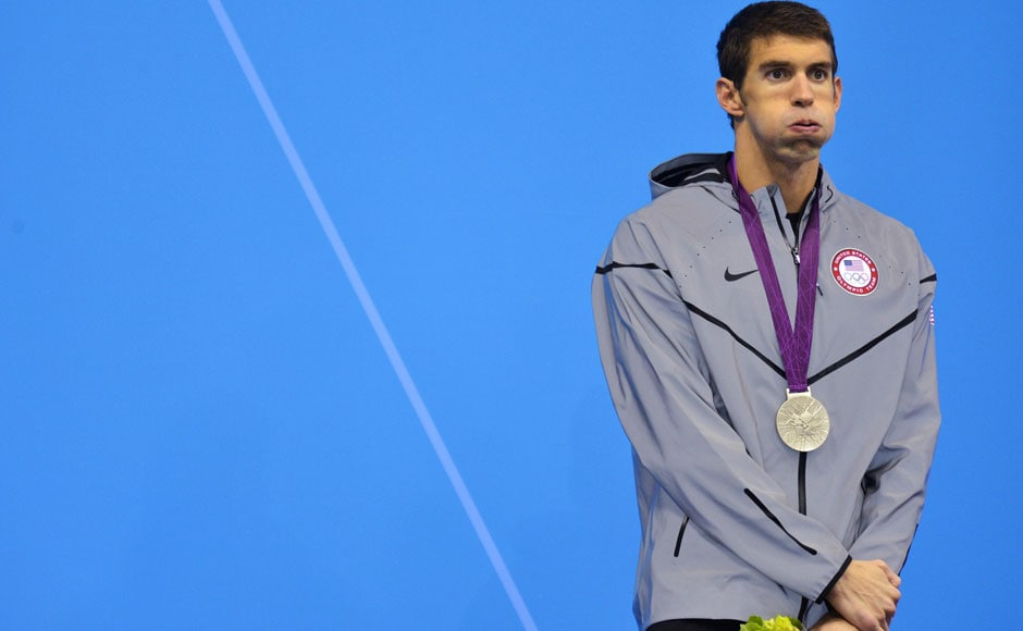 Michael Phelps of the U.S. puffs his cheeks after receiving his silver medal on the podium during the men's 200m butterfly victory ceremony. Toby Melville/Reuters