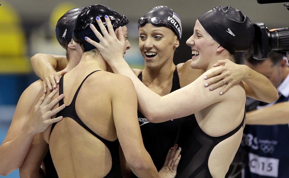 United States' Shannon Vreeland, left, and Missy Franklin, right, embrace Allison Schmitt, foreground, and Dana Vollmer, center, after they won gold in the women's 4x200-meter freestyle relay swimming final at the Aquatics Centre.Matt Slocum/AP