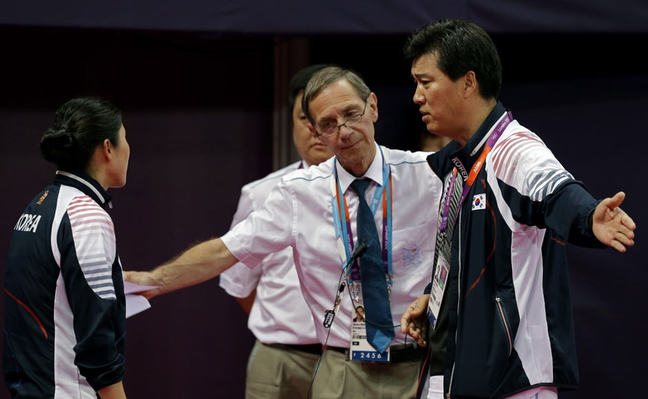 Head badminton referee Torsten Berg, second from right, talks to South Korea's head badminton coach Sung Han-kook, right, after Berg issued a black card to the players in the women's doubles badminton match between South Korea's Ha Jung-eun and Kim Min-jung, and Indonesia's Meiliana Jauhari and Greysia Polii .AP