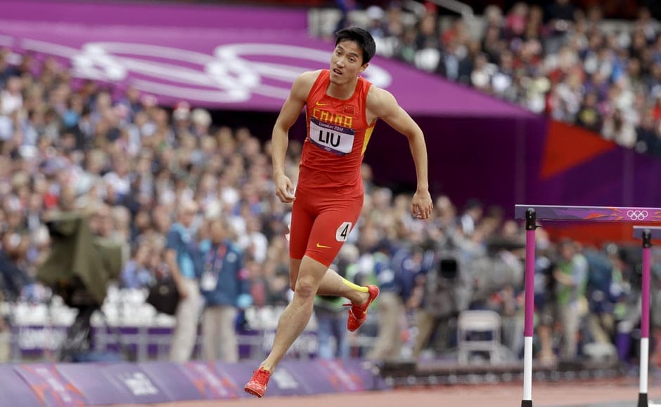 China's Liu Xiang hops off the track after falling in a men's 110-meter hurdles heat during the athletics in the Olympic Stadium. AP