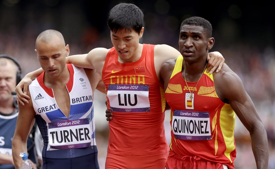China's Liu Xiang is helped off the track by Britain's Andrew Turner, left, and Spain's Jackson Quinonez after falling in a men's 110-meter hurdles heat. AP