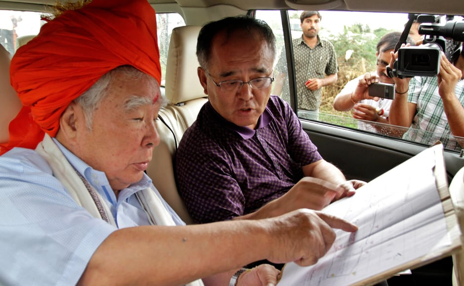 Osamu Suzuki goes through the site map with an unidentified official. AP
