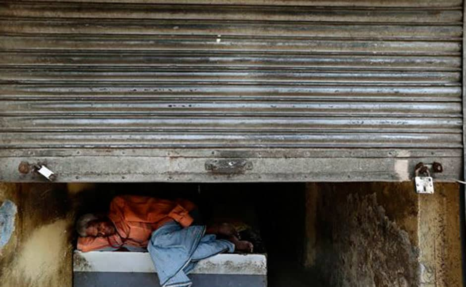 A man rests in a shop with shutters half closed during a nationwide strike in New Delhi. AP