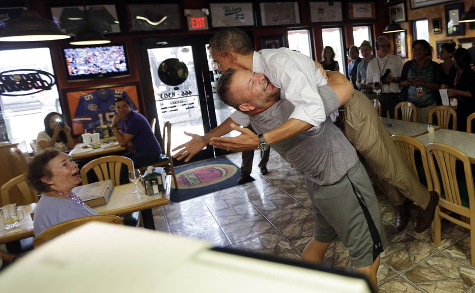 Its bear hug time for Obama:President Barack Obama is picked up and lifted off the ground by Scott Van Duzer, owner of Big Apple Pizza and Pasta Italian Restaurant, during an unannounced stop. AP