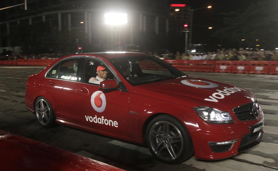 British Formula One driver Lewis Hamilton, drives a car with the winner of Vodafone Speed Fest, a promotional event in Mumbai.Rajanish Kakade/AP
