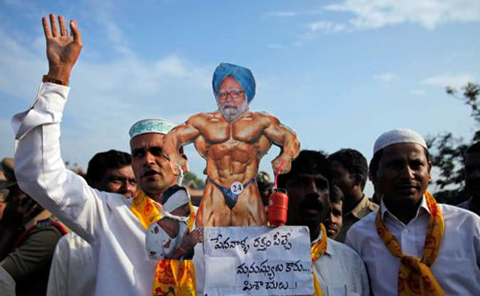 "TDP activists carry a caricature of Prime Minister Manmohan Singh with the words ""the blood suckers are not human beings but devils"" during a protest at a bus station in Hyderabad. AP"