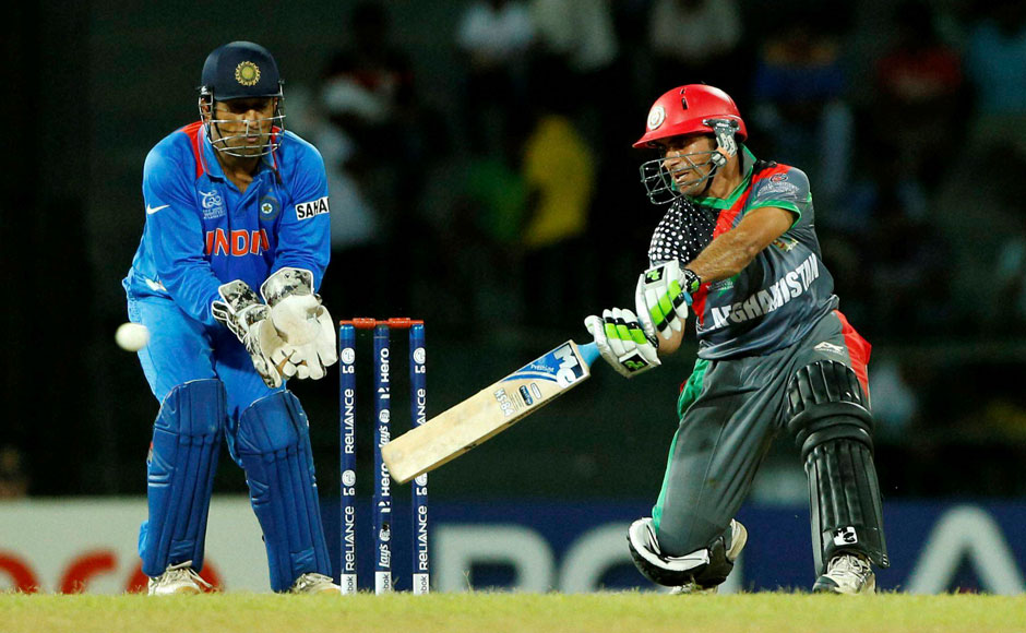 Afghanistan's batsman Karim Sadiq, right, plays a shot as Mahendra Singh Dhoni watches during their ICC Twenty20 Cricket World Cup on Wednesday. AP