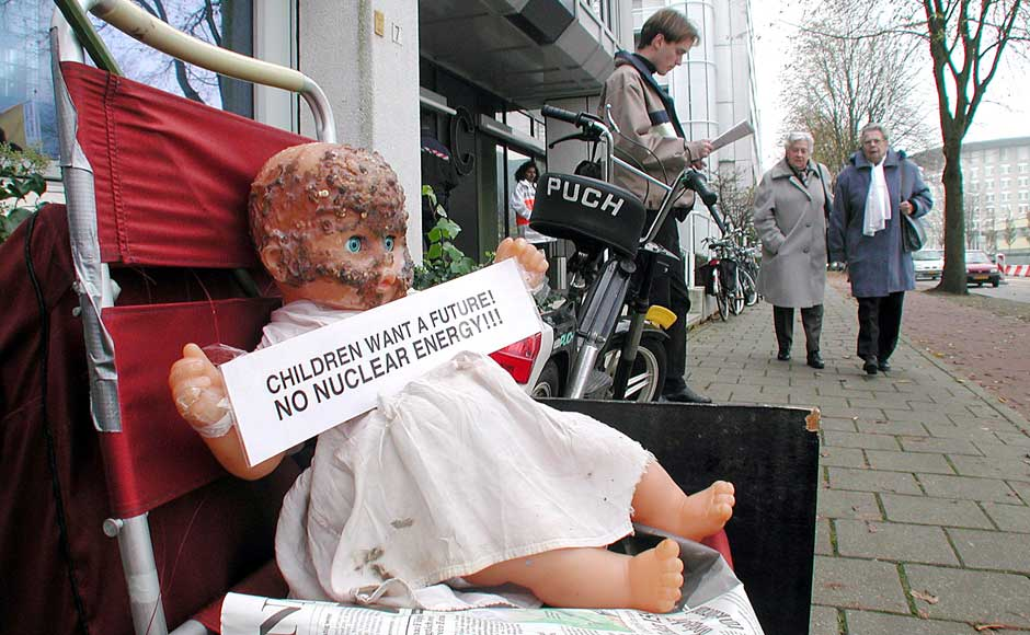 <br />Pedestrians walk towards a burnt doll place there by an anti-nuclear protester outside the 6th United Nations Conference on Climate Control 14 November 2000 in The Hague, The Netherlands. Michel Porro/Newsmakers