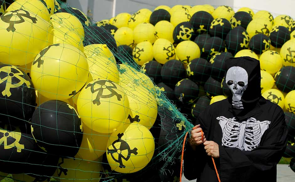 <br />An activist wearing a skeleton costume holds balloons with radiation symbols on them tethered prior to releasing them at an anti-nuclear demonstration outside the Chancellery on 5 September 2010 in Berlin, Germany. Sean Gallup/Getty Images