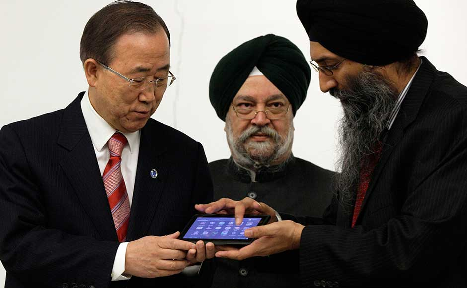 (Read their lips! Ban Ki-moon to Tuli: Are you sure its working?) Suneet Singh Tuli, right, CEO of Datawind, presents UN Secretary General Ban Ki-moon, left, an Aakash2 tablet computer during a meeting at the United Nation headquarters. They are accompanied by India's UN Ambassador Hardeep Singh Puri. Richard Drew/AP