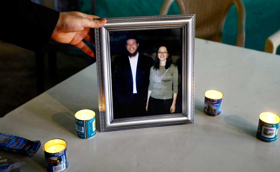 A Jewish man holds up a photo of Rabbi Gavriel Holtzberg (left) and his wife Rivkah (right) who were killed during the Mumbai attacks, after offering prayers at the Chabad (Nariman) house on its fourth anniversary in Mumbai. AP