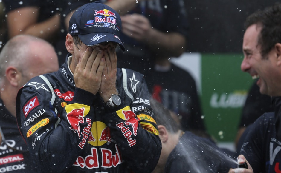 Champagne sprayed on Vettel as he celebrates winning the world championship. Reuters