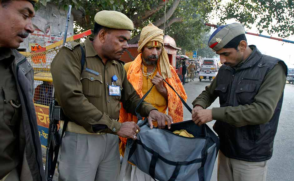 Policemen check the luggage of a Hindu holy man at the town border on the eve of the anniversary of the Babri mosque demolition in Ayodhya. Rajesh Kumar Singh/AP