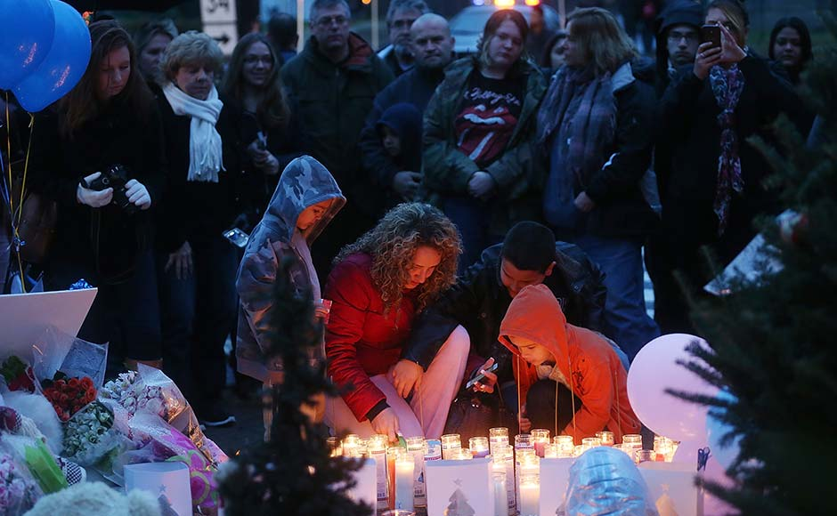 People gather at a memorial for victims near the school on the first Sunday following the mass shooting at Sandy Hook Elementary School. Mario Tama/Getty Images