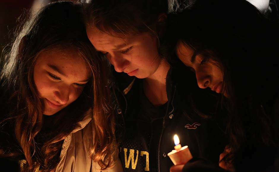 Kate Suba, left, Jaden Albrecht, center, and Simran Chand pay their respects at one of the makeshift memorials in honour of the victims of the Sandy Hook Elementary School shooting. Mary Altafer/AP